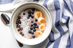 Top View Food Photo of Healthy Breakfast Smoothie Bowl with Banana, Blueberry and Coconut Rasp