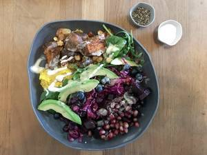 Top View Food Photo of Healthy Vegan Rainbow Bowl with Sweet Potato, Avocado, Pomegranate, Red Cabbage and Blueberries on Wooden Table