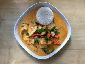 Top View Food Photo of Spicy Thai Tofu Curry with Rice, fresh Vegetables, Coconut Milk and Cream