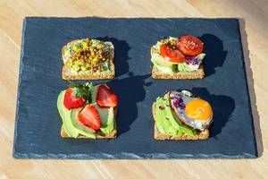 Top View Food Photo of Toast with Avocado, Lentils, Strawberries, Corn, Tomatoes and Sunny Side Up Egg on Black Cutting Board