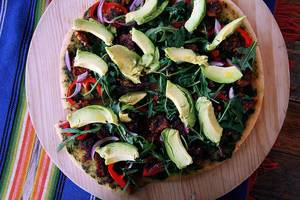 Top View Food Photo of Vegan Pizza with Arugula, Bell Pepper and Avocado on a Wooden Board