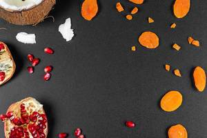 Top view, frame of dried apricots, pomegranate and coconut on a black background