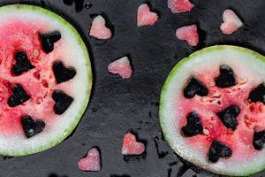Top view fresh watermelon with cut heart shaped pieces on black background (Flip 2019)
