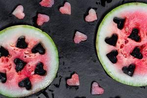 Top-view frische Wassermelone - mit geschnittenen herzförmigen Teilen auf schwarzem Hintergrund