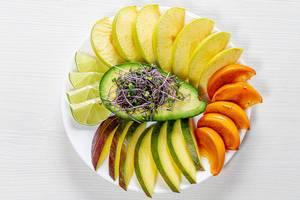 Top view fruit slicing on a white plate with avocado and micro green cabbage in the middle (Flip 2019)