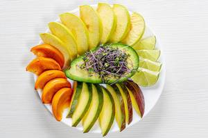 Top view fruit slicing on a white plate with avocado and micro green cabbage in the middle
