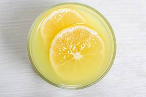 Top view glass of lemon juice with a slice of lemon on white wooden background