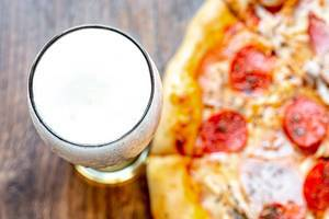 Top view glass of light beer and pizza on wooden background (Flip 2019) (Flip 2019)