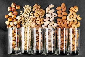 Top view, glasses with pistachios, almonds, cashews, walnuts, pine nuts and hazelnuts on a black background (Flip 2020)