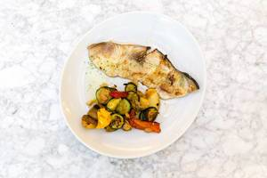 Top View - Grilled swordfish with vegetables on a white plate on granit background
