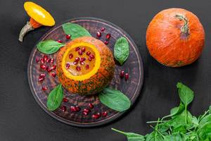 Top view Halloween concept-pumpkin with pumpkin puree, spinach and pomegranate on black background (Flip 2019)