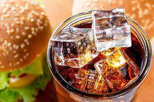 Top view ice cubes in a glass with a drink and burgers