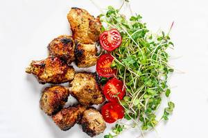 Top view meat kebab with micro-green radish and tomato slices on a white plate