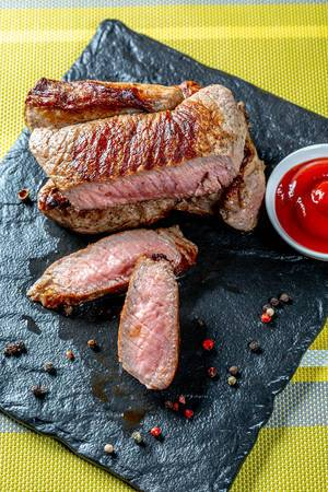 Top view medium roast steak sliced with sauce and spices on a stone tray