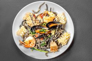 Top view noodles with cuttlefish ink in creamy sauce with seafood (Flip 2019)