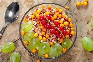 Top view oatmeal porridge with fresh sea buckthorn berries, red currants and grapes (Flip 2019)