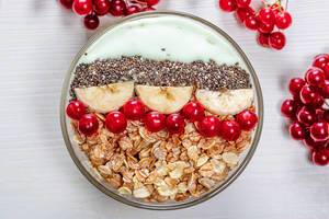 Top view oatmeal with Chia seeds, viburnum berries and banana slices