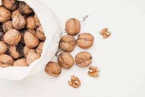 Top view of a bag of walnuts on white background