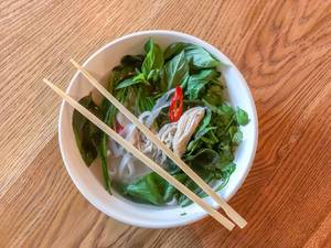 Top view of a bowl of Pho Ga Vietnamese chicken soup
