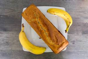 Top view of a box-shaped banana bread next to two whole bananas