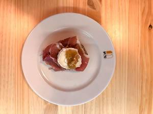 Top view of a bread snack with serano ham, soft cheese, jam and a walnut on a white plate