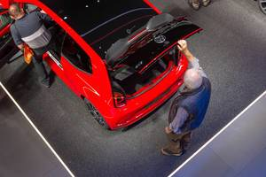 Top view of a red VW Up! GTI: Man opens the trunk with roof spoiler