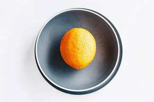 Top view of a single orange in a grey plate .