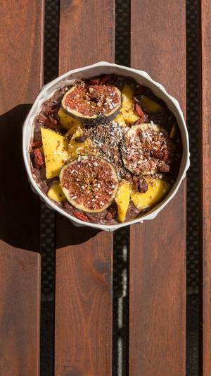 Top view of an Acai Bowl with mango, figs, raisins, goji berries and shredded coconut