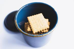 Top view of biscuits in a metal jar on white background