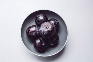 Top view of blue plums in a grey bowl. White background.