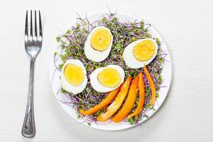 Top view of boiled eggs with micro greens and pieces of bell pepper in a plate on a white wooden background with a fork (Flip 2019)