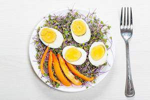 Top view of boiled eggs with micro greens and pieces of bell pepper in a plate on a white wooden background with a fork