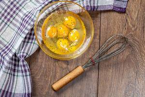 Top view of broken chicken eggs in bowl with whisk on wooden background