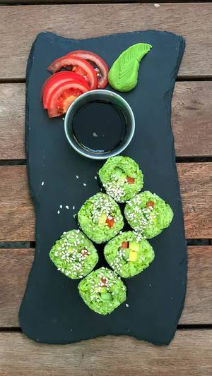Top view of California rolls served on black stone at Avocado Cafe