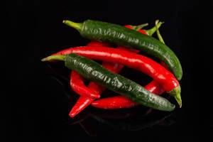 Top view of Chilli Hot Peppers above black background