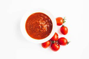 Top view of chopped tomatoes sauce in a bowl and fresh cherry tomatoes on white background