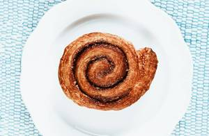Top view of cinnamon roll in white plate.