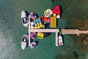 Top view of colourful rubber dinghies and water toys at Kolimbithres Beach on Paros, Greece