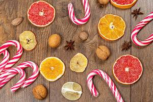 Top view of dried slices of citrus fruit, nuts, and candy cane on wooden background (Flip 2019)