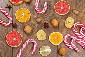 Top view of dried slices of citrus fruit, nuts, and candy cane on wooden background