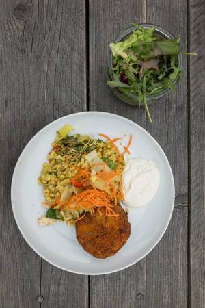 Top view of eggplant-potato croquettes, veggie risotto with tarragon aioli and mixed salad