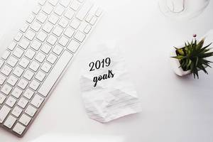 "Top view of flat lay with keyboard, plant and paper with ""2019 goals"". New year concept."