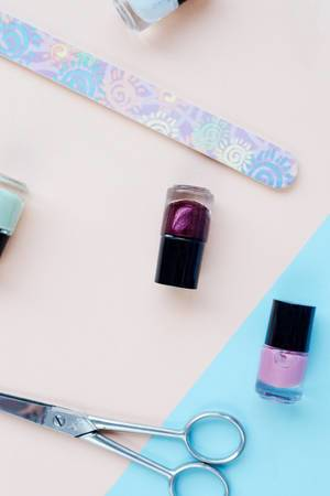 Top view of flat lay with nail polish and manicure accessories. Colorful background.