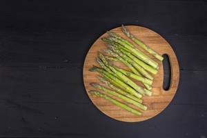 Top view of Fresh Asparagus on the round wooden board with black background with copy space