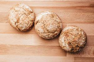 Top view of fresh baked wholemeal crusty bread rolls on a wooden board