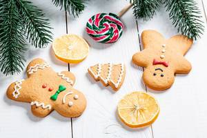 Top View of gingerbread men next to Lemon Slices, Lollipop and Tree Branches on a white wooden Table