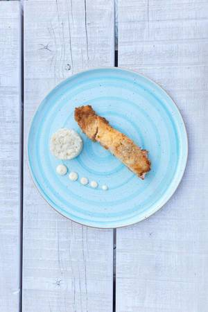 Top view of gratinated salmon with parmesan crust, dark rice and wasabi mayonnaise