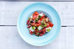 Top view of Greek salad with tomato, cucumber, dry onion, sun-dried tomato, feta cheese, capers and olive oil