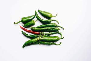 Top view of green and red chili peppers on white background
