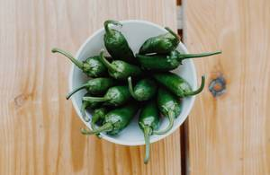 Top view of green spicy peppers on a wooden background
